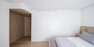 Built-in storage lines the master bedroom. The headboard and bed frame are also custom units from Mecanismo, fashioned from oak, brass, and Kvadrat upholstery.