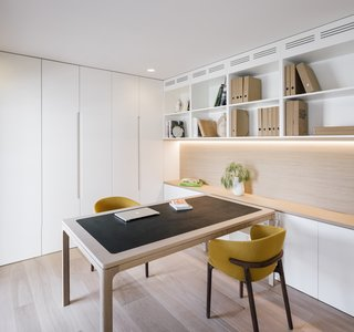 The office features built-in bookshelves and storage, plus a table by Jardin.