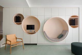 The highlight of Atelier Pierre Louis Gerlier's renovation is the living room wall which discretely hides storage cabinets and features four circular pale-pink, built-ins, one of which serves as a cozy reading nook.