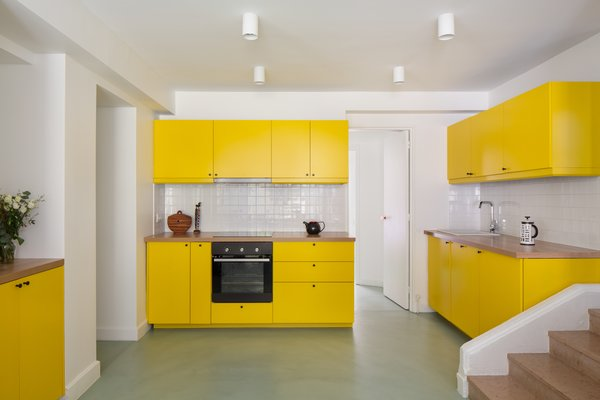 "Gerlier chose to recycle the original Ikea kitchen by simply repainting the laminate fronts bright yellow and adding a wood countertop. The sunny shade was chosen to brighten the space and ""add cheerfulness to a sometimes very dark room""."