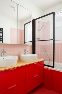 The bathroom was updated with retro-looking pink tiles, which were unconventionally paired with a red vanity and floors.
