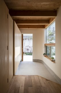 The entrance to the home—the genkan—is where guests remove their shoes in a Japanese house. Here, it conveniently features built-in storage cabinets.