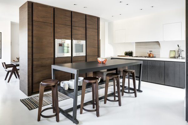 The kitchen is the perfect example of Graham's streamlined aesthetic.It features a custom, freestanding storage unit and countertops made from Macaubas granite and Fenix NTM.