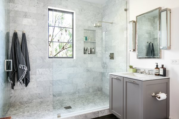 The bath also features a spacious glass-enclosed, marble-tiled shower.