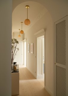 The handblown glass and brass pendant lighting in the hallway is by Douglas & Bec.