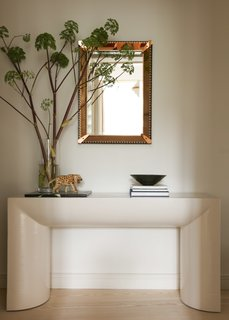 A lovely hallway vignette consists of a Karl Springer console and a mirror from Fontana Arte.