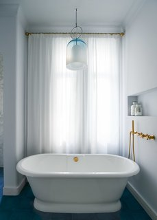 A blown glass and chrome pendant light by Carlo Nason for Mazzega hangs above the soaking tub.