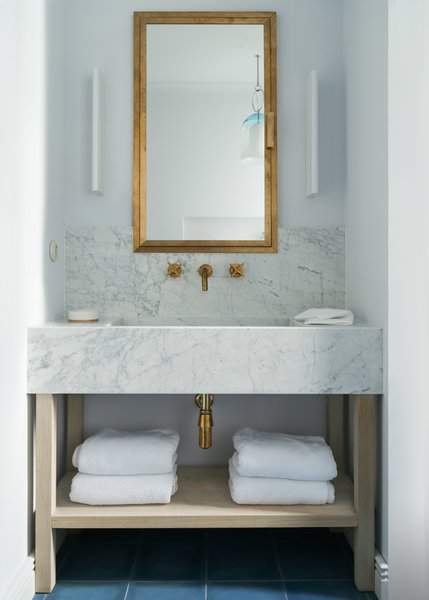 The bathroom is a mix of marble and brass with a custom vanity.