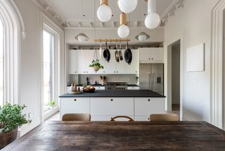 The minimalist kitchen features Richlite countertops and Ikea PAX cabinets with Reform Basis fronts in matte white.