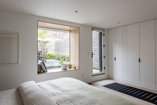 A window in the garden-level master bedroom was enlarged, increasing the amount of natural light that enters the room. The built-in closets feature IKEA PAX components with custom fronts in matte white to match the walls.