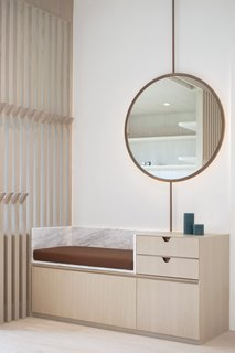 This custom storage bench with a built-in cabinet and mirror was designed and fabricated by Bean Buro. The unit is made from wood, marble, and an upholstered leather seat. It's designed to create a moment of pause when arriving or leaving the apartment.