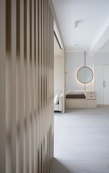 The timber slatted dividers serve double duty by supporting bookshelves in the living room and coat hooks at the entry.