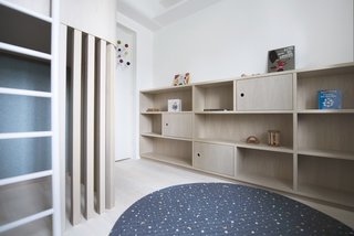The walls of the room are lined with easily-accessible shelves and cabinets that are perfect for books and toys.