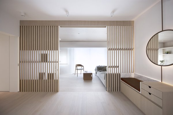 The slatted dividing wall creates a distinction between the living room and the entryway, which is essentially part of a larger open space that includes the dining area.