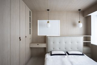 In the master bedroom, Bean Buro encased the couple's existing bed in a timber unit. The JWDA Pendant is by Menu.
