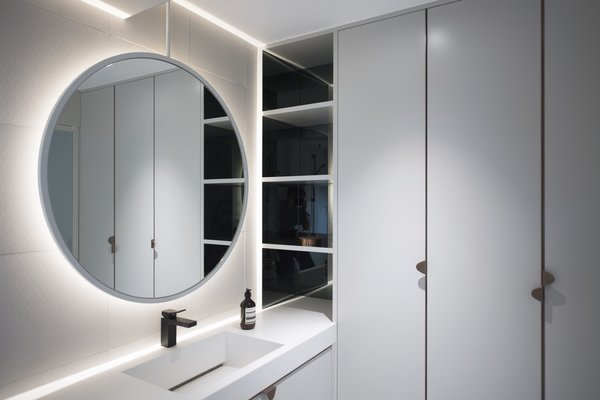 The master bathroom also has ample storage and a large, circular mirror.