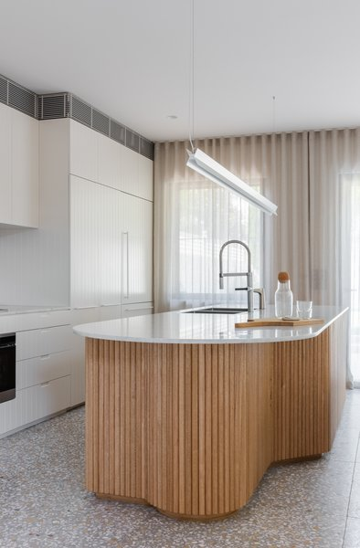 "The kitchen island was handcrafted with 30-millimeter Tasmanian Oak half-round dowels. ""The [curved form] became a real feature of the house which was mimicked in details such as the timber island and doorway threshold,"" explains Peake. The countertop is Carrara marble from Avant Stone."