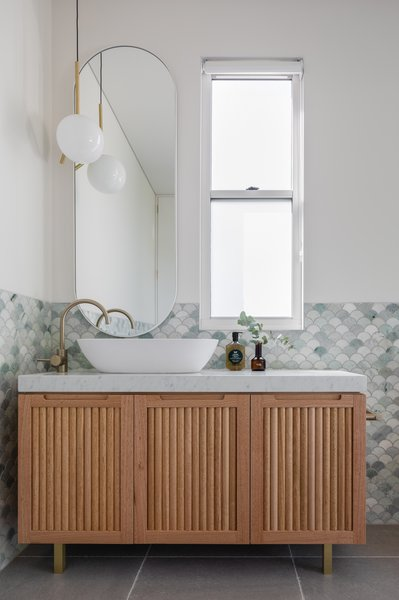 """The wall of the master bathroom is tiled with Ming Green Marble Fan Tiles from Tera Nova, paired with tumbled limestone floor tiles from Tera Nova. A Michael Anastassiades Flos pendant light from Living Edge brightens the space. The bespoke vanity was designed by Carter Williamson and built by House by Hart Joinery. """"Again, we used timber half-dowels to tie the look in with the kitchen,"""" says Peake."""