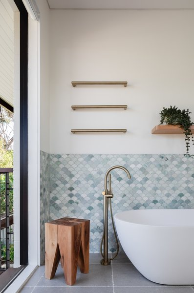 The full-height glass sliding door leads to a balcony that overlooks the backyard. The wall is tiled with Ming Green Marble Fan Tiles from Tera Nova.