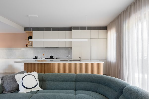 """""""We always like to do floor-to-ceiling curtains: we feel it's softer and more intentional,"""" says Peake. The light above the island is a Span Linear Pendant from Living Edge."""