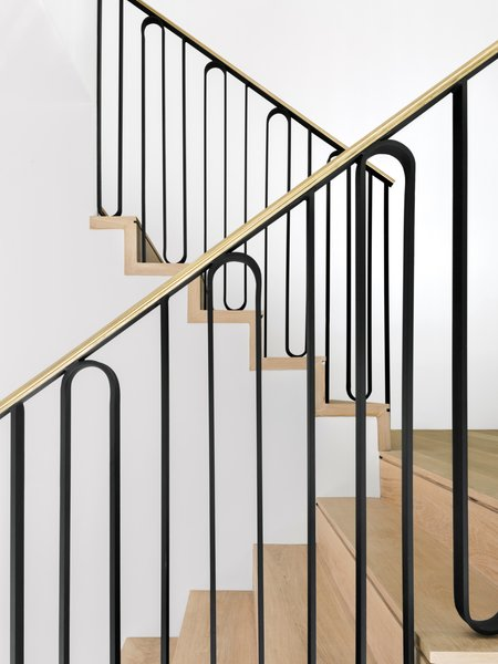 The staircase handrail was custom designed by Unicus Developments specifically for this renovation. It's constructed from a combination of iron and unlacquered brass. The craftsman applied a step notch—a linear cutout—to each stair tread.