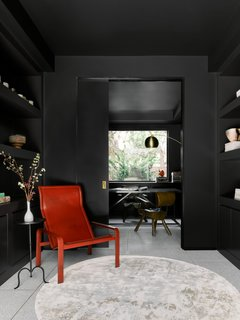 The library and home office space were painted a bold shade of black. The red leather Golfo dei Poeti lounge chair is by Matteo Grassi.