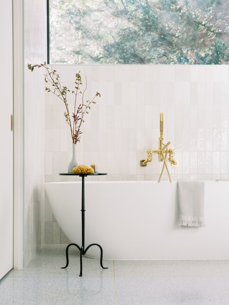 A deep soaking tub and a large picture window add to the bathroom's luxurious vibe.