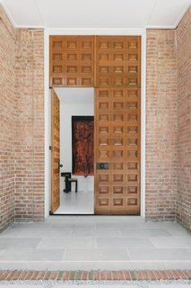 "The original door was removed during the renovation, restored, and then replaced toward the project's completion. The carved wood door is 11 feet tall, and Uzcategui says it adds ""a distinctive element essential to the home's history and sense of style."""
