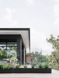 "Outside, the glass border almost disappears, so as not to interfere with the architecture of the home. ""It's a full glass panel that meets all safety codes with planters at the bottom for added warmth and dimension,"" explains Uzcategui."