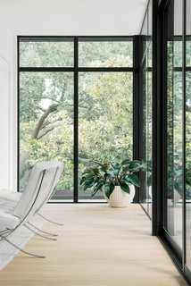 Full-height windows wrap the room, and glass sliding doors lead to the terrace.