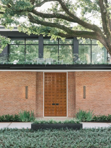 "The glass-wrapped, upper-level addition came to Uzcategui as an epiphany as he stood on the roof of the home. The ""tree room"" now grows out of the original brick structure as if it was destined to be there all along."