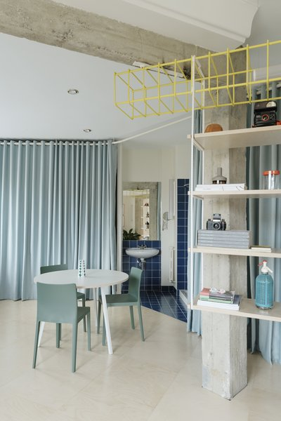 One of the apartment's two bathrooms is tucked behind a curtain adjacent to the kitchen.