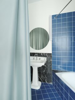 The bathroom is tiled a bold blue, with repurposed Nero Marquina marble which was originally part of the kitchen flooring.