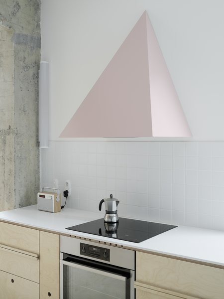 Color was a fundamental element of the project and the pink range hood certainly makes a bold statement. The birch plywood boards that are used for the kitchen cabinetry match the flooring and reflect the firm's embrace of DIY techniques.