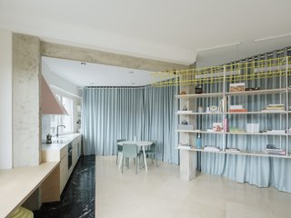 AZAB tore down the walls of the 969-square-foot flat using curtains to define and separate the living spaces. They also chose to embrace the unit's gentle curve and incorporate it into their design.