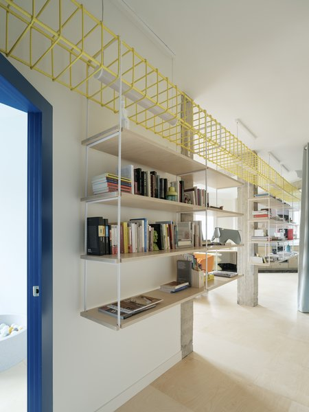 The bookcase is suspended from a bright yellow structural frame that runs the length of the apartment and down the hallway.