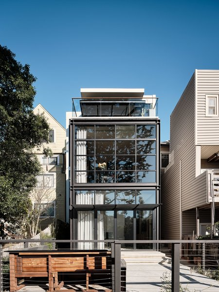 """The ultra-modern, glass-and-steel back facade now """"acts as an oversized southern aperture and fully retractable gateway"""" for the home, says Hackett."""