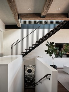 A walnut-and-steel staircase leads to the upper level. Massive, upcycled, old-growth Douglas fir beams line the ceiling.