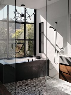The master bathroom features cement Cigar Shop tiles by Clé Tile. The tub is made of black-honed absolute granite with plumbing fixtures by Dornbracht. The lighting is the Double Octopus by Autoban for De La Espada.