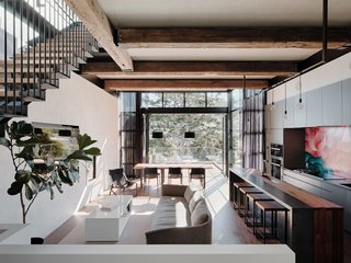 The great room is designed for indoor/outdoor living. The floor-to-ceiling glass wall at the back of the space (which is just a slice of the all-glass rear) includes a bi-fold NanaWall door system that opens the home to an outdoor terrace and the lush surroundings.