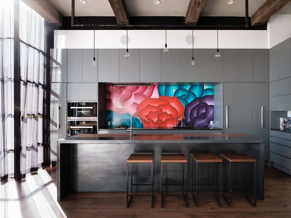 Síol Studios designed the custom lighting system and walnut-and-steel kitchen island, which was fabricated by Trojan Woodworking. A vibrant mural by Bay Area artist Jet Martinez enlivens the space, and the bar stools are from Ohio Design.