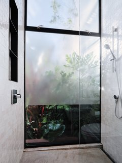 """On the garden level, a bathroom with Moroccan tiles and glass walls simulate the feel of an outdoor shower. """"The shower offers one of the few architectural opportunities for a true pause,"""" says Hackett. """"It slows down mind-space and body-space at once, and amplifies both."""""""