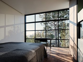 "The master bedroom features a large grid of windows that ""gets likened to Dürer's Device (an early method for understanding perspective),"" shares Hackett."