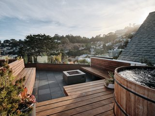 The dreamy rooftop looks out over Noe Valley. Built-in redwood benches surround a concrete fire pit; the bluestone pavers are part of a Bison deck system. An oversize, barrel-like teak hot tub from Roberts Hot Tubs allows for a soak in the garden-like setting, which features plants selected and installed by Danielle Coulter of Collecting Flowers.