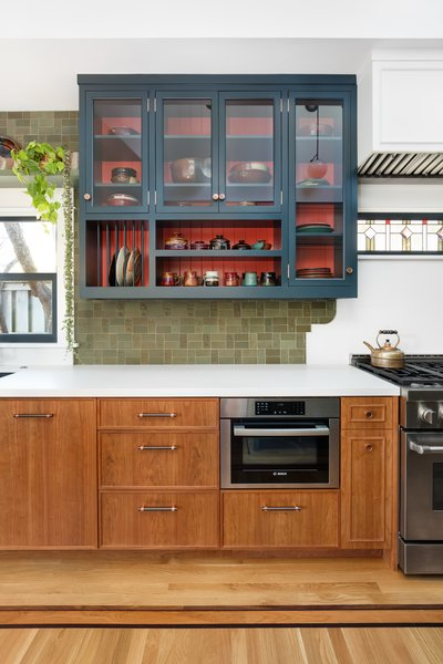 """Custom cabinetry was added to meet Hixton's kitchen needs. """"We measured all her jars, the plates, everything,"""" says Dyer. The color palette was largely guided by a client-provided velvet pillow and Jackson's signature red-glazed pottery."""