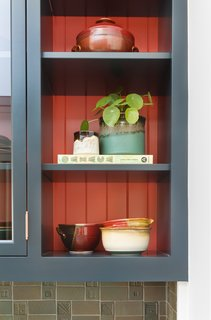 The open upper cabinets and shelves function as storage and double as displays for Jackson's pottery.