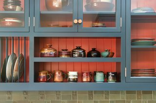 The upper cabinets and display shelves in the kitchen are home to some of homeowner, Barrett Jackson's creations.