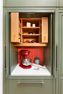 The pantry doors open to reveal an extra-high level of customization where every inch of storage space is thoughtfully accounted for. What looks like two pull-out drawers below the space are actually three drawers, as one door actually containing two drawers inside it.