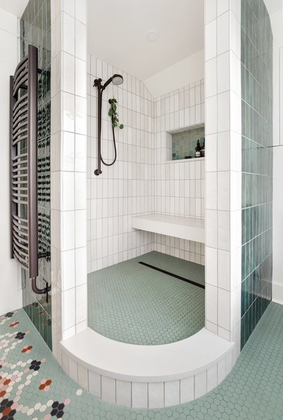 The elegantly curved shape of the open shower in the master bathroom came from the couple's desire to not have to deal with cleaning a glass door or having a curtain. The opening also allows some natural light to enter the shower. The vertically-positioned rectangular tiles are from Portland company Clayhaus Modern Tile.