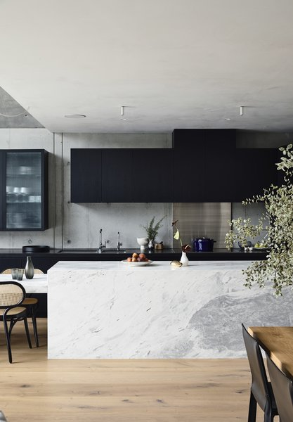 The sleek marble island pops against the black cabinetry—all of which was custom designed for the space. The rear countertop is made from black Zimbabwe granite. The flooring is oak timber in a custom 320 mm width.
